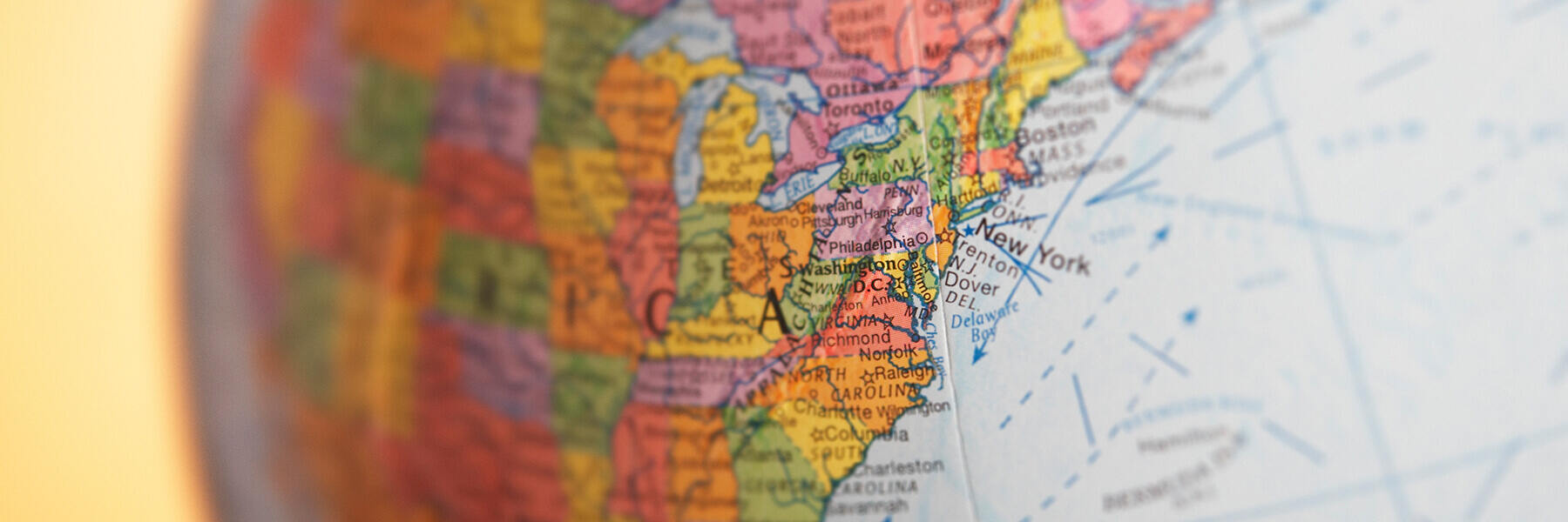A close-up of a world globe, focusing on the east coast of the United States of America.
