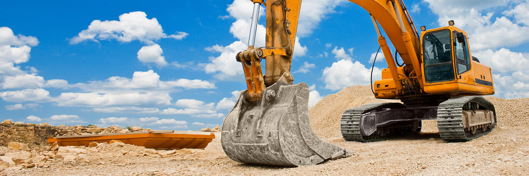 A yellow excavator sits on a dirt lot in front of partly cloudy  blue skies.
