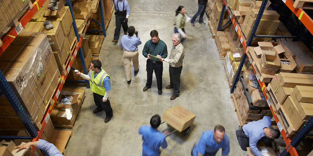 Two business men standing checking inventory list in warehouse aisle behind worker scanning shelving stacked with boxes