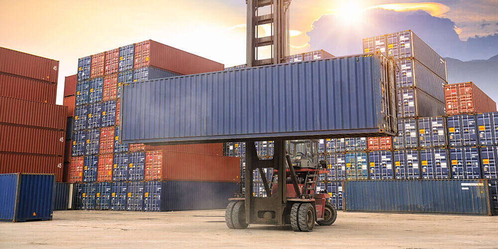 Crane loader on wheels lifting large grey cargo container surrounded by stacks of orange and grey shipping containers