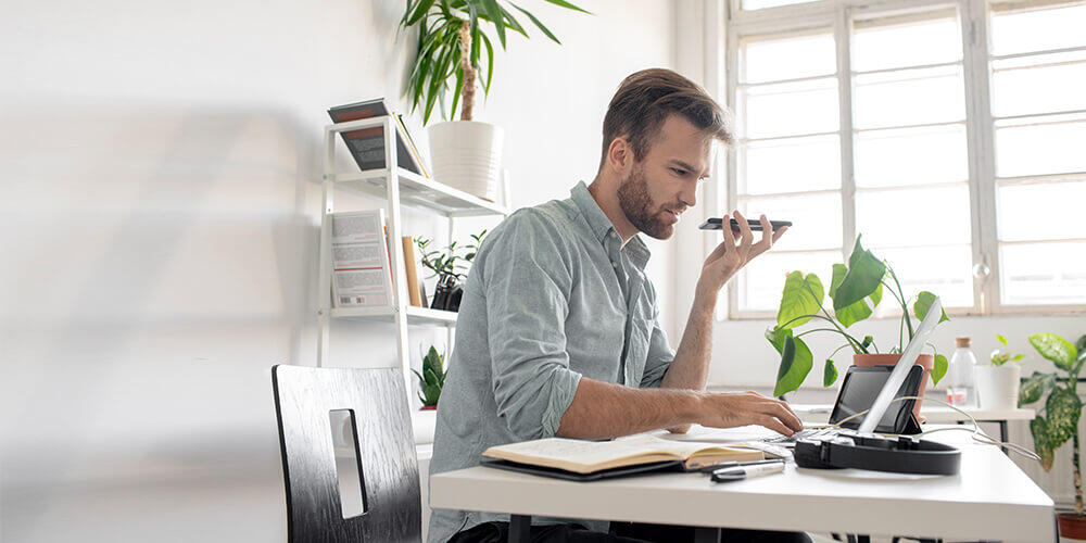 A business man with a beard sits in a bright room with plants and talks on his cell phone while typing on his laptop