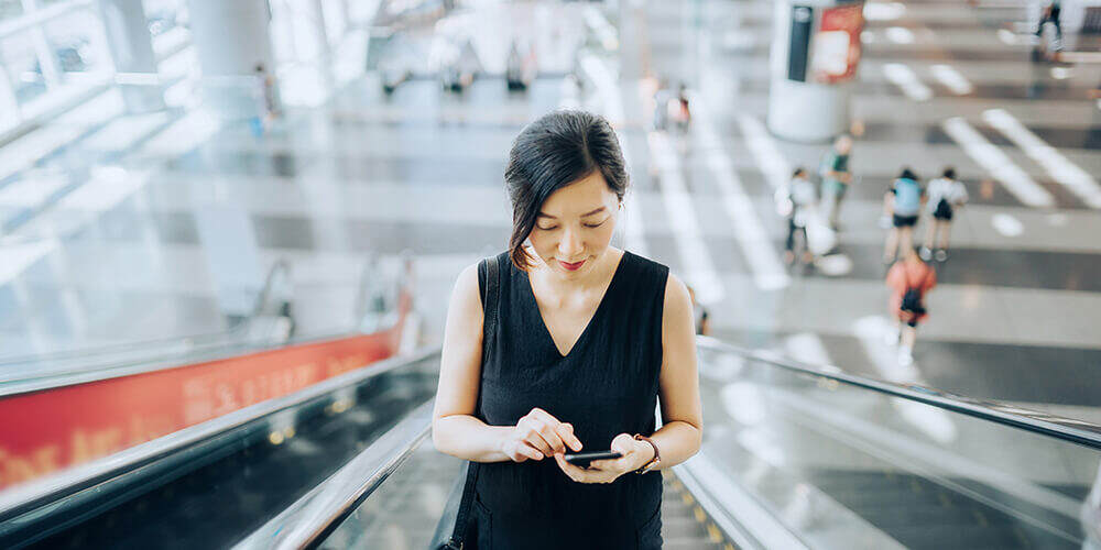 Woman in sleeveless black dress riding up escalator while looking down to use mobile phone
