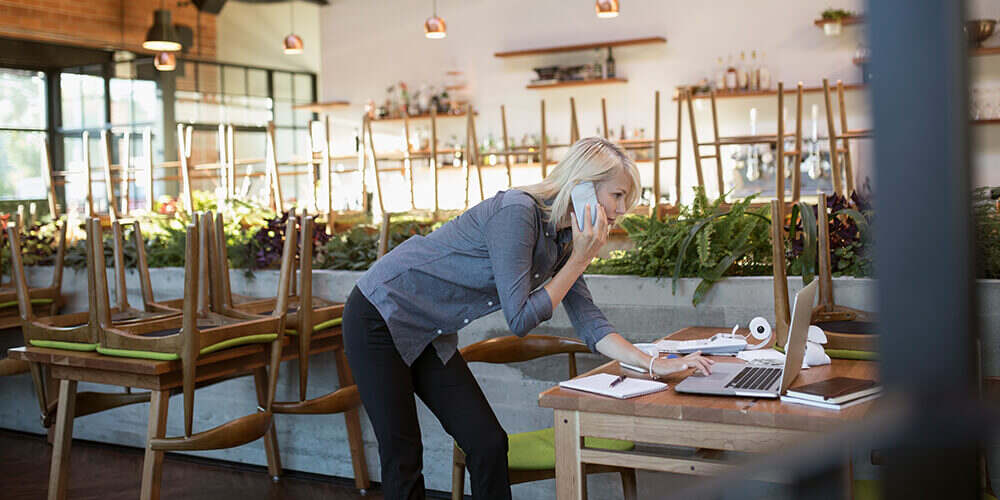 Blond woman on phone stands over laptop, notebook and adding machine working in closed, brightly lit casual restaurant