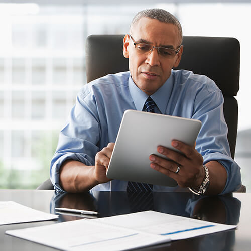 Business man in glasses and blue shirt with tie sitting at desk in big leather chair holding tablet