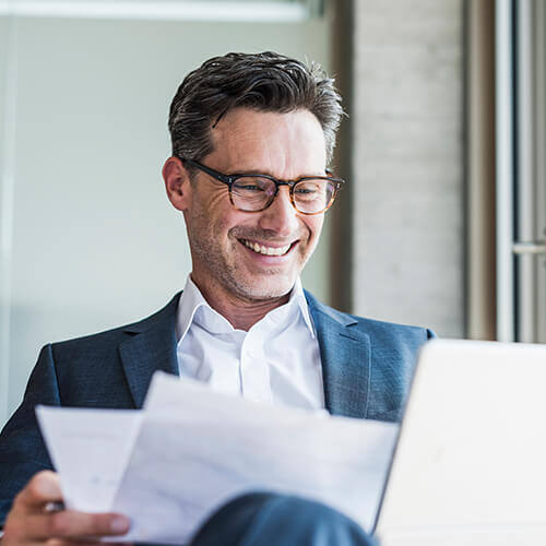 Business man with salt and pepper hair and tortoise shell glasses sits back smiling at papers with open laptop on desk