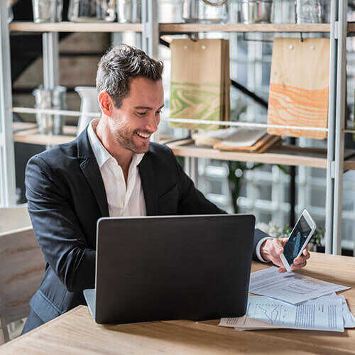 Business man in dark jacket and partly unbuttoned white shirt sitting in workspace with laptop smiling down at mobile phone