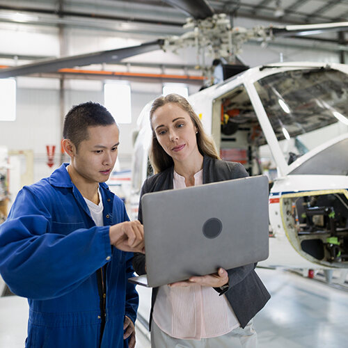 Aircraft maintenance mechanic in blue jacket confers with business woman holding laptop in aviation hangar