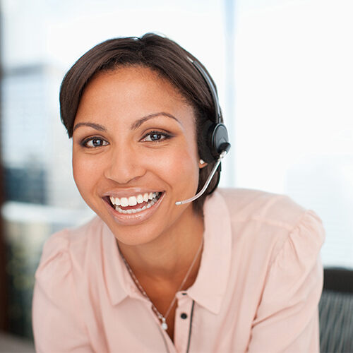 Business woman in a light pink blouse wears a headset as she smiles at the camera