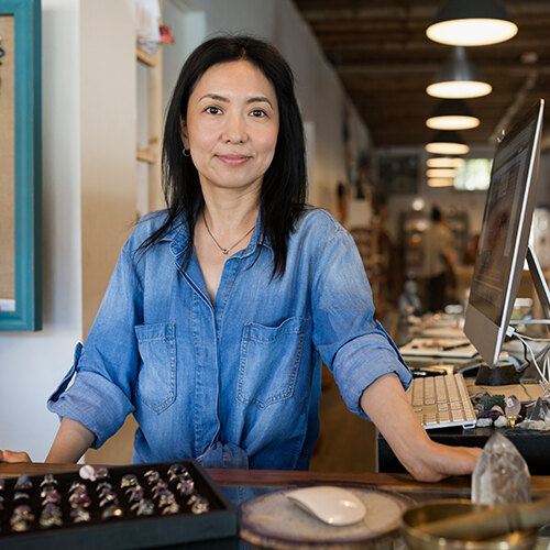 Female jewelry store owner in blue denim button-up stands at customer counter smiles  pleasantly at camera