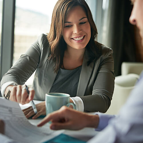 Business woman in grey suit sits holding pen and smiling at table with businessman and cup of coffee while reviewing paperwork