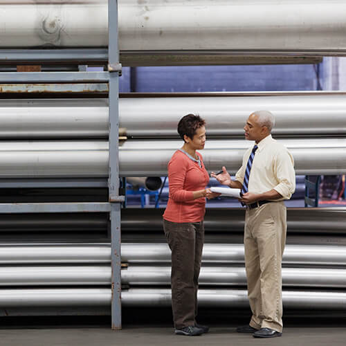 A business man and business woman standing in warehouse facility holding notebook while discussing business