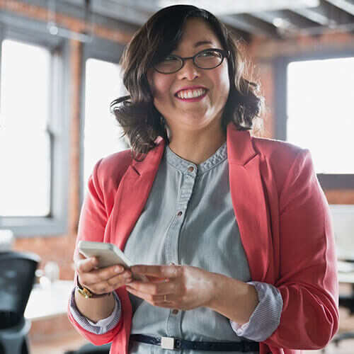 Business woman in dark glasses and pink jacket standing in office smiling looking up from mobile phone