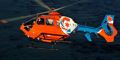 Pilot and co-pilot fly bright orange helicopter aircraft with blue and white markings over water