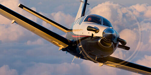 Pilot turns airborne turboprop aviation aircraft with yellow under wings to the left in late afternoon sun