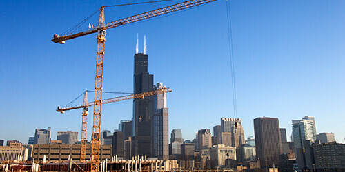 Two yellow cranes standing idle in foreground of city with tall black building reaching up into bright blue sky