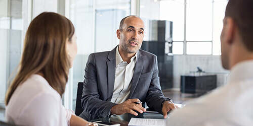 Balding man in gray jacket and no tie sitting at meeting table talking to two business colleagues listening in foreground