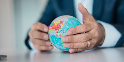 Close-up on the hands of a business man wearing a gold band, sitting at desk with a miniature globe