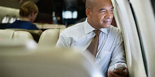 Smiling bald businessman in white shirt and brown tie seated and gazing out of small private jet airplane window