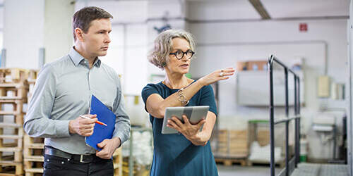 Business man with blue notebook and pen listening to business woman with short hair and glasses holding tablet