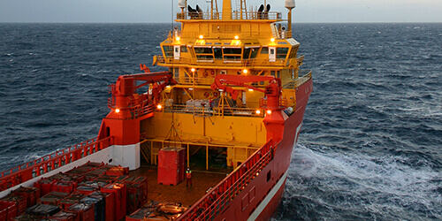 Large freighter with red hull with white stripe and yellow decking cuts through open ocean on grey cloudy day