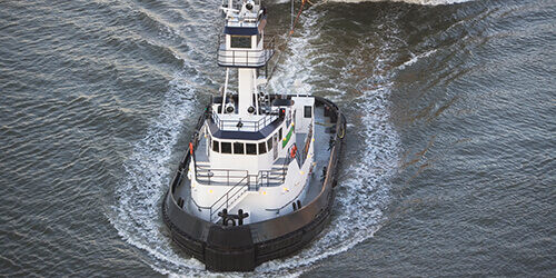 Overhead view of marine tugboat cutting through water pulling large black barge with yellow bow