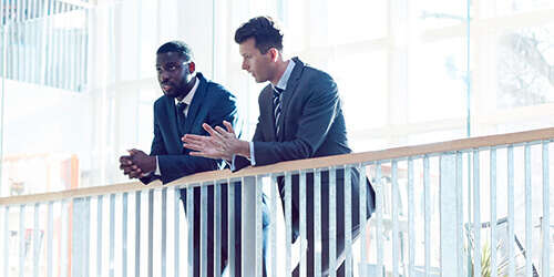 Two business men lean on a railing in a brightly lit atrium and have a thoughtful conversation.