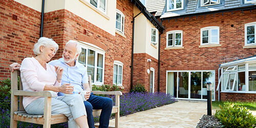 Elderly couple sit together on wooden bench drinking coffee and talking outside of well-kept brick senior living facility