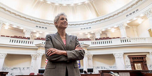 Female government official smiles while standing with arms crossed gazing across empty state capital building