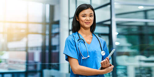 A young female nurse in blue scrubs with a stethoscope around her neck holds a tablet as she stands in a hospital corridor with windows.