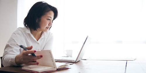 A business woman in white sits by a bright window with her laptop and takes notes in a planner