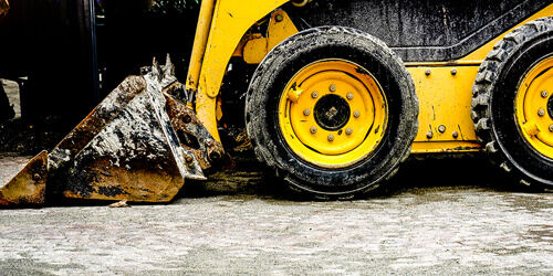 A close-up view of a yellow bulldozer, covered in dirt after a day of digging.