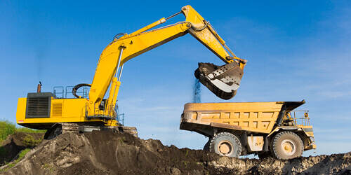 A yellow excavator truck pours dirt into a yellow dump truck as the two clear out an area of land.