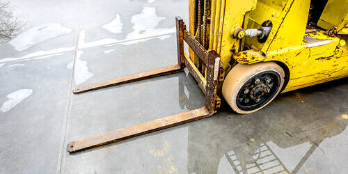 An empty yellow forklift is parked outside rainy concrete.