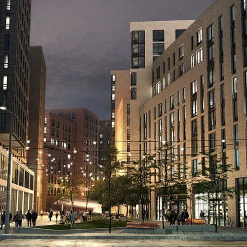 Multi-store apartment buildings lit up at night overlooking well-kept public park space filled with pedestrians