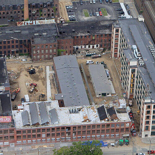 Aerial view of development construction converting former brick mill factory complex into community residential housing