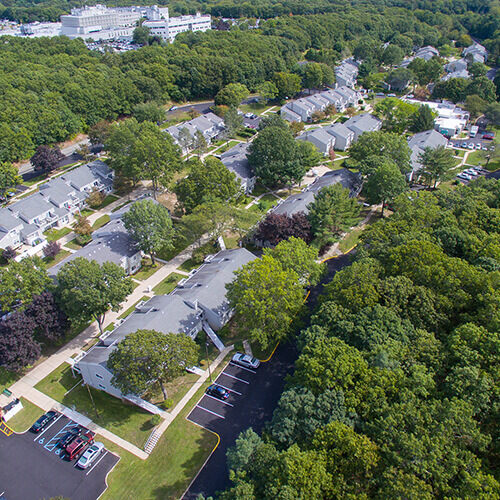 Aerial view of residential condominium housing development Sienna Village with gray rooftops and leafy green trees