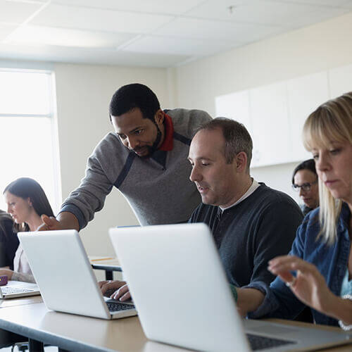 Classroom of adults sitting in front of laptop computers while instructor leans over man's shoulder looking at screen