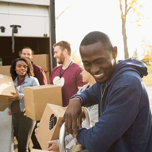 Male volunteer in navy hooded sweatshirt standing smiling helping other volunteers unload boxes from back of delivery truck
