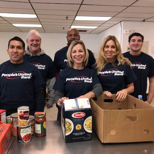 Mixed group of People's United Bank employees in navy t-shirts volunteering at food bank preparing brown boxes with pantry food