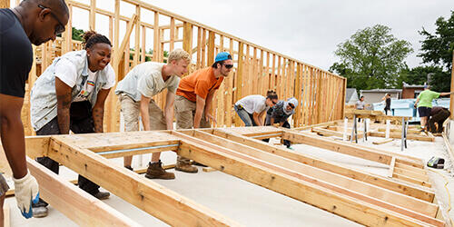 Group of volunteers standing inside a new construction project bending down getting ready to lift into place a framed wall