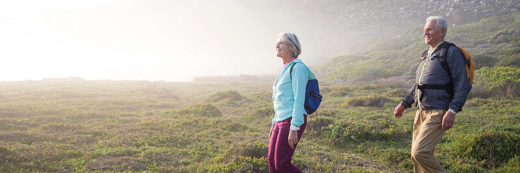 Mature man and woman wearing backpacks hike down a grassy hill with fog and rocks in the background