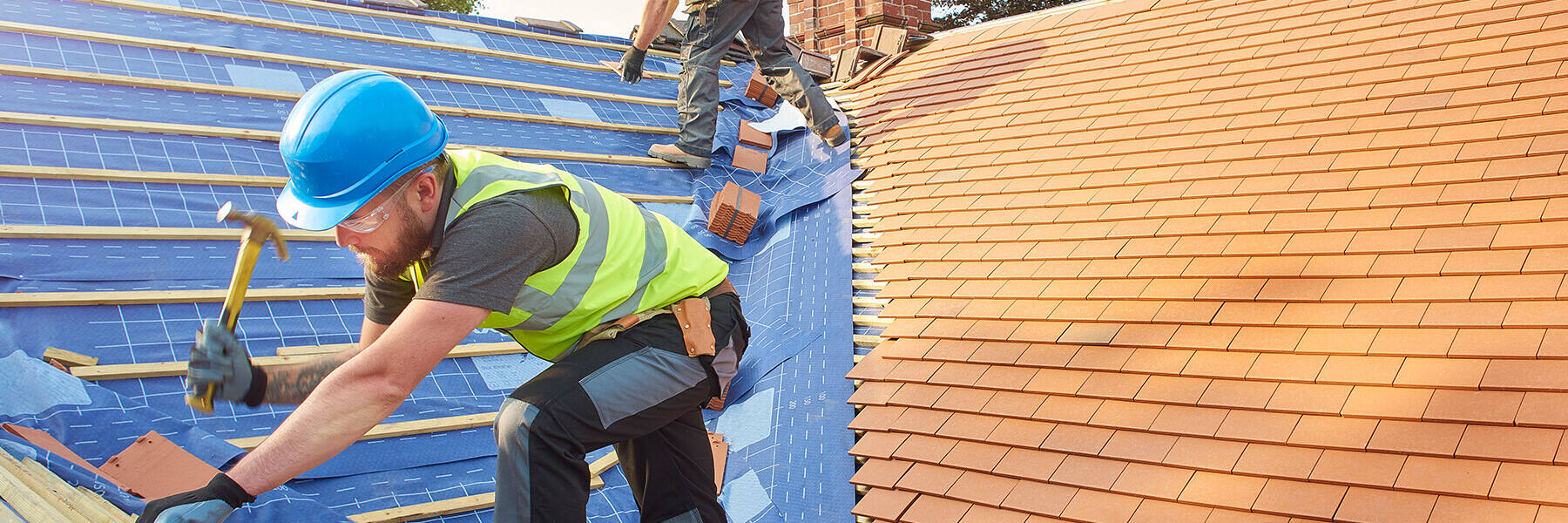 Construction worker wearing blue hard hat bends over to hammer a new roof on a residence