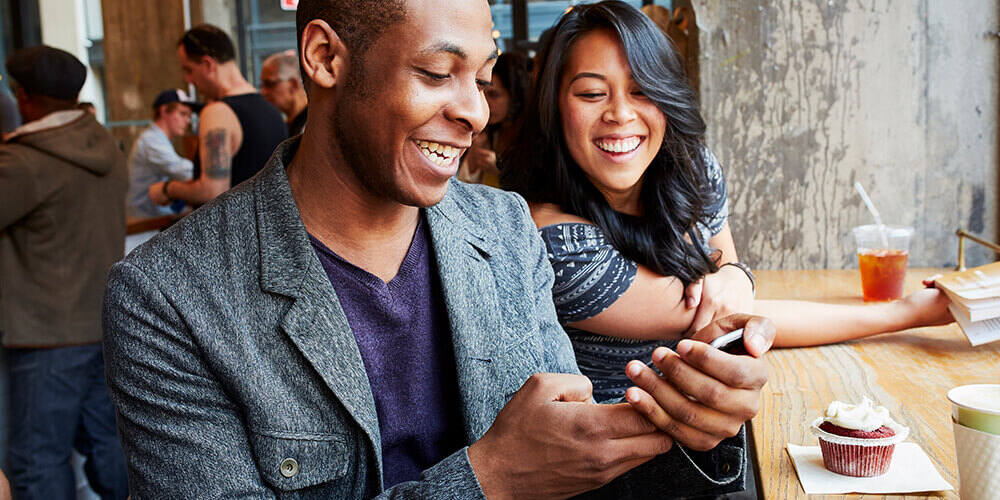 Two young happy people seated at a casual restaurant smiling while looking at his mobile phone