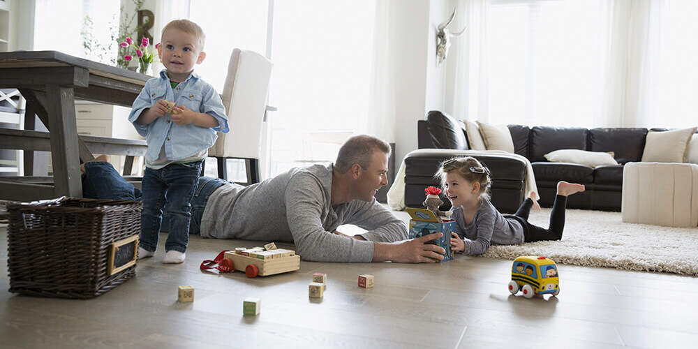 A dad lays on the floor as he plays with toys with his two young children