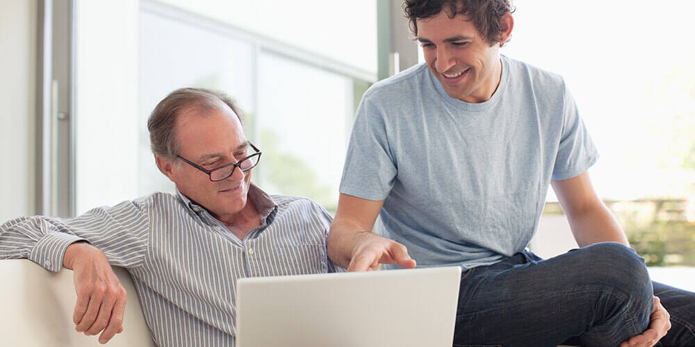 An older father in a button down shirt and glass and his adult son in a light blue t-shirt sit on a couch review a laptop.