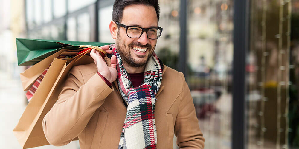 Fashionable man with beard and glasses smiles as he walks down the street with shopping bags over shoulder