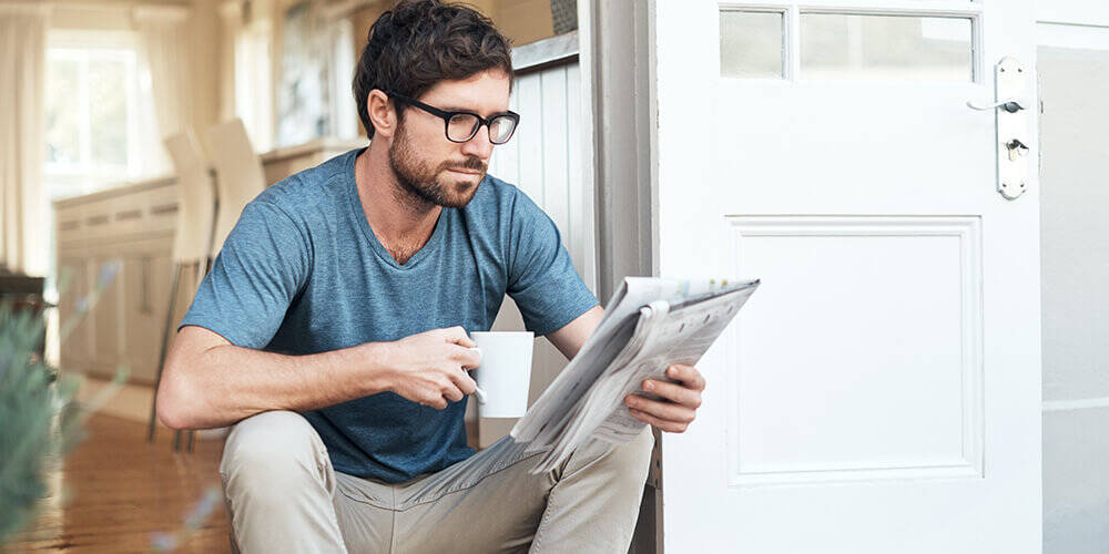 A man in a tshirt and glasses sits in his front doorway with coffee and the newspaper