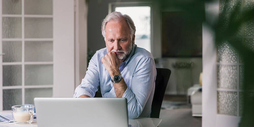 A senior man wearing a light blue shirt and watch sits in his home and looks at his laptop with concern