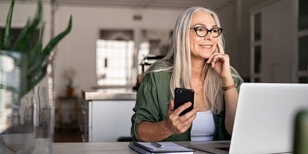 A senior woman with long white hair and a green shirt and glasses holds a phone and her laptop as she stares away smiling