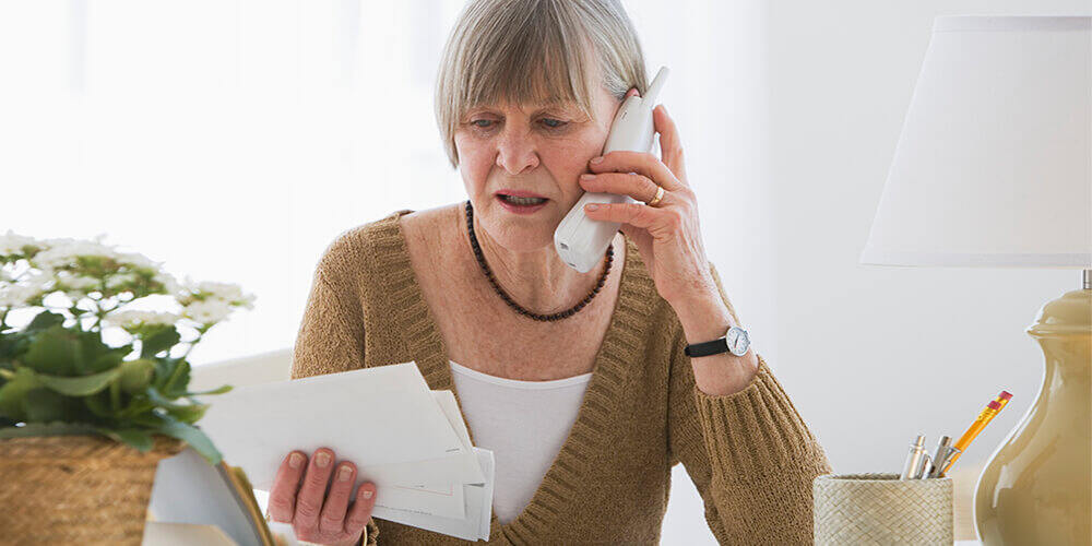 A senior woman wearing a watch and green sweater holds a pile of mail and looks worried as she makes a phone call